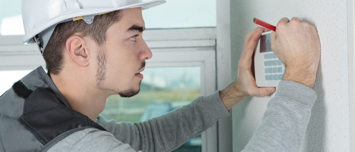 worker installing alarm system in office