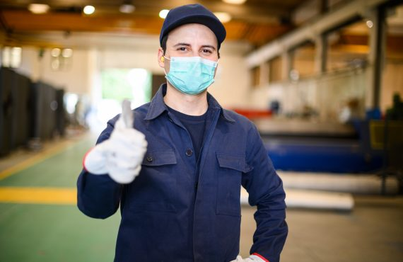Portrait of a worker in an industrial plant wearing a mask and giving thumbs up, coronavirus concept