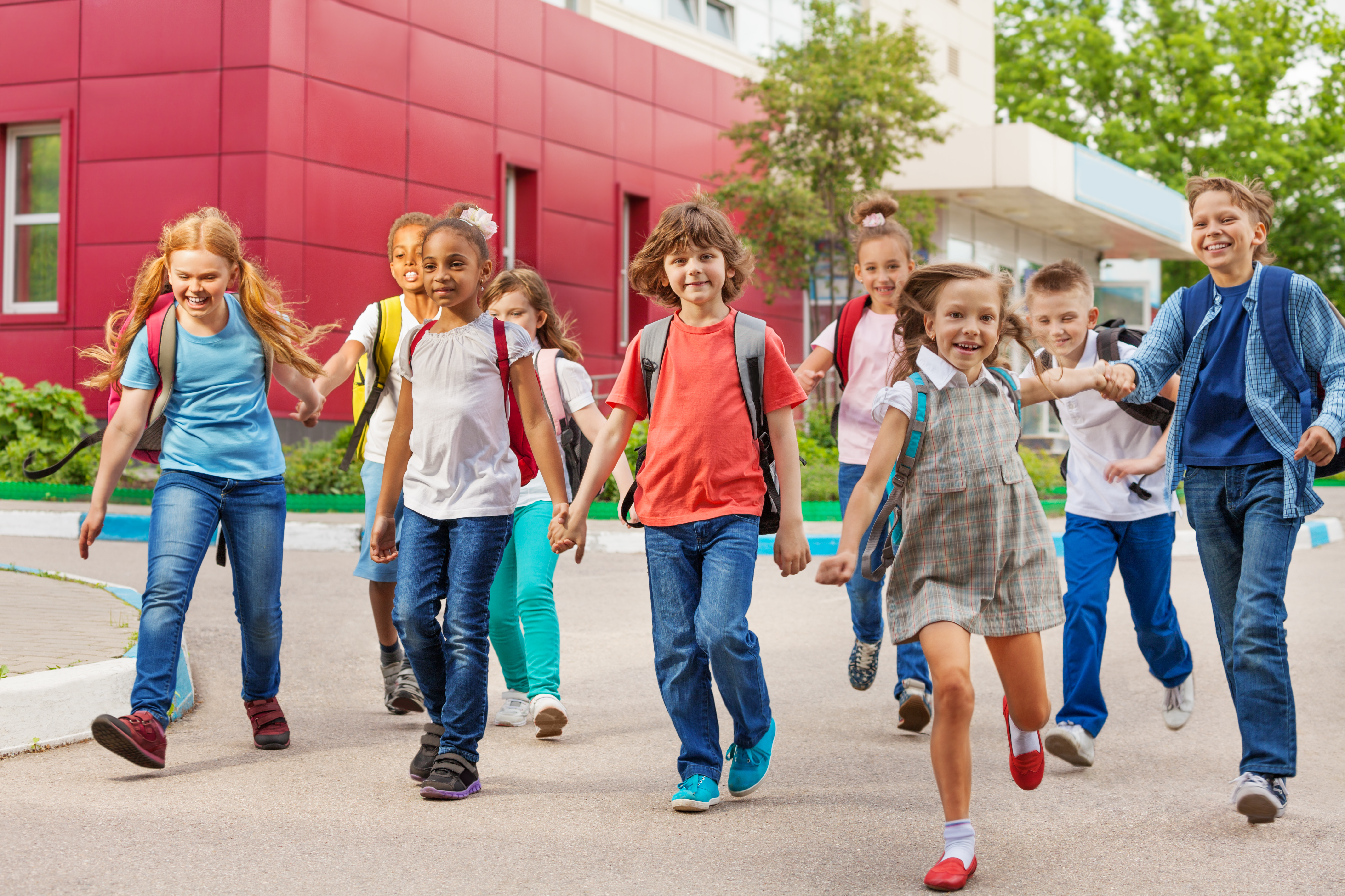Happy kids with rucksacks walking holding hands near school building during summer day time